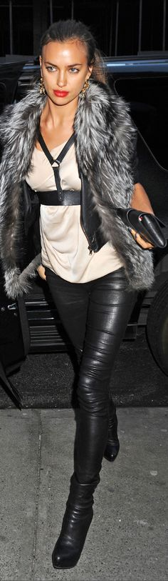 Model Irina Shayk in a fur vest, leather jacket, cream colored silk blouse, Agent Provocateur body harness, leather pants, leather Christian Louboutin boots and a Hermes Medor clutch.