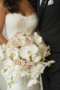 "The bride carried a bountiful bouquet composed of light pink ""Quicksand"" roses, white orchids, and ivory stephanotis blossoms dotted with crystals. #WeddingBouquet Photograph by: Images by Berit, Inc. Read more: https://www.insideweddings.com/weddings/luxurious-summer-wedding-at-the-pierre-new-york/378/"