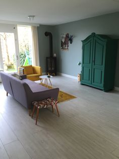 Paarse sofa van sofacompany. Okergele rozenkelim. Kast geverfd in patina green. Kleur op de muur is early dew.