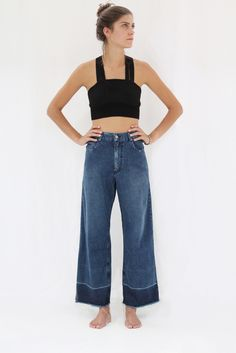 Tanktop and jeans. The black tubetop-like garment leaves no space for well-defined breasts.
