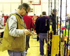 Jen Marra / Herb Williscroft of Little Egg Harbor eyes up a fishing rod from the display table of Reel Life Bait and Tackle of Point Pleasant during the Ocean City Intermediate School Fishing Club's Fishing Flea Market Saturday, March 7 in the school gymnasium. All proceeds from the event go to the fishing club.