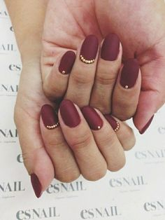 two hands with deep red matte nail polish, decorated with golden rhinestone details
