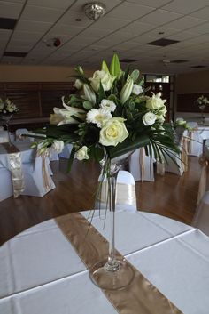 Martini vase arrangments of roses, lilys and lisianathus  www.weddingflowersbylaura.com