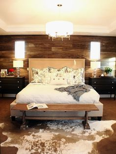 Richly stained wood wall boards create a rustic backdrop in this cozy, neutral bedroom. An upholstered headboard softens the look.