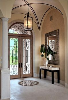 Barrel vaulted entry with gorgeous natural stone floors with stone inlay. Love the wrought iron inserts/leaded design of these front doors. Great mix of old style architecture meeting contemporary furnishings.