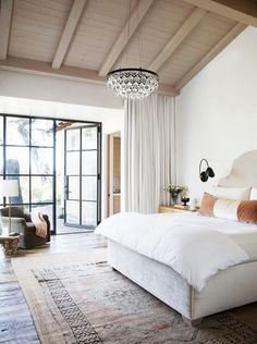 Bedroom with high ceilings, a chandelier, a velvet headboard, and layered rugs