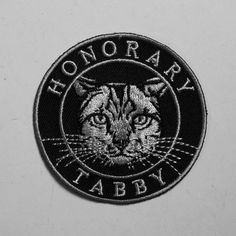 """HONORARY TABBY tabby cats are sweet and neurotic; sound like anyone you know? - 2.5"""" embroidered patch - grey on black - sew it to your sweater - made in toronto"""