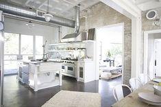 cocina, abierta de estilo industrial, muebles color blanco, electrodomésticos con acabado en acero inoxidable, paredes de ladrillo visto, suelo microcemento