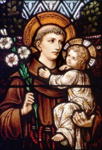 Photo of a stained glass image of St. Anthony of Padua and the Christ child.