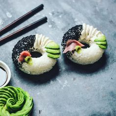 grease a donut mould with coconut oil, mould in cooled sushi rice and then gently remove by lifting the pan upside down. Decorated with black sesame, ginger, wasabi, cashew, mayo and avocado.