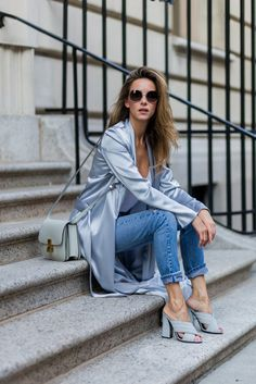 A satin blue trench with a camisole top, jeans, and sandals.