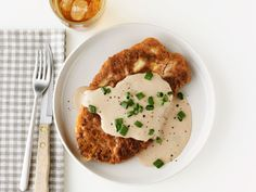 Chicken-Fried Steak With Cream:  Ingredients  For the gravy:  2 tablespoons unsalted butter  2 tablespoons vegetable oil  1/3 cup all-purpose flour  2 1/2 cups whole milk  Kosher salt and freshly ground pepper  For the steak:  4 beef cube steaks (1 1/2 to 2 pounds total)  Kosher salt and freshly ground pepper  1 1/2 cups all-purpose flour  2 teaspoons baking powder  1 cup whole milk  2 large eggs  Vegetable oil, for frying  Sliced scallions, for topping (optional)