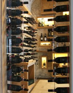 Bottles behind glass enclosed custom wine cellar featuring Cable Wine System.