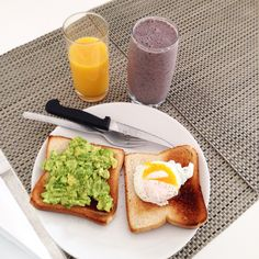 Avocado and poached egg on toast with smoothie: spinach red fruits and banana