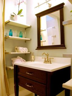 Narrow wall shelves are an excellent way to store bathroom essentials in a stylish way. Invest in attractive canisters to hold cotton swabs, cotton balls and your favorite lotion, and place unsightly toiletries under the vanity. Small wicker baskets can also be placed on the shelves for additional, hidden storage. Design by John Gidding
