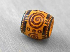 hand-painted wood dreadlock hair or jewelry bead in curry yellow with brown and black tribal patterns
