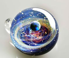 Satoshi Tomizu, a talented glass artist in Japan, creates stunning cosmic scenes in tiny glass pendants no larger than your eyeball. Air bubbles, opals, flakes of gold and other inclusions turn each glass bubble into a busy galactic microcosm.