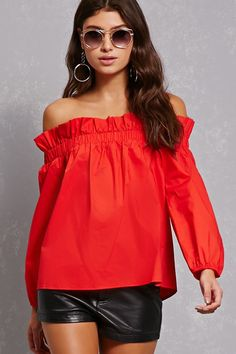 A woven top featuring an elasticized off-the-shoulder top with ruffled trim and long sleeves.