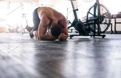Muscular man tired after intense in crossfit gym. Bodybuilder taking break after crossing training.