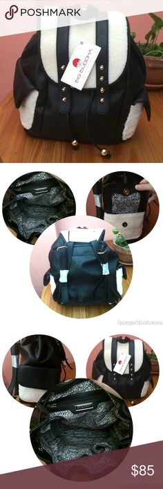 """Big Buddha Black and Off-White Backpack City style and room for everything. Vegan leather & faux shearling exterior. Bag features one handle, two adjustable backpack straps, one exterior slip pocket, two fold over side exterior pockets, one interior zip pocket and two interior open pockets, gold tone hardware, cinch straps and top flap snap closure. Approximately 13"""" H x 10"""" W x 6.2"""" D without straps. Big Buddha Bags Backpacks"""