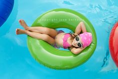 a bright colored swim ring is the perfect summer prop for a cute picture of your child at the pool...take photo from above as child relaxes on their back in the colorful inner tube