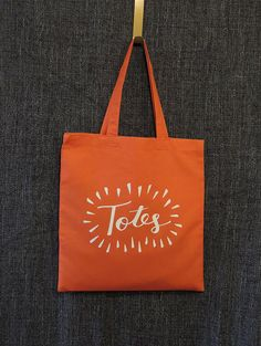 This tote bag is made of 100% cotton and features a hand type graphic that says Totes. It measures 15W x 16H and is the perfect size to tote around while shopping.