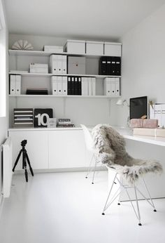 Just about my dream office. The monochrome shelf organisation, the chair with sheepskin, the splash of pale pink, everything.