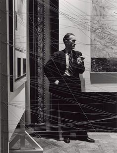 """Marcel Duchamp photographed behind his installation """"sixteen miles of string"""" New York, 1942, photo by Arnold Newman"""
