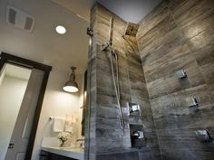 Porcelain tile designed to look like weathered barn wood lines the spacious shower enclosure. Placing the tiles horizontally creates a modern look.