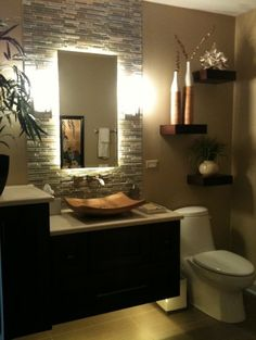 Wall mounted vanity with lighting underneath, tile & mirror, sconces.