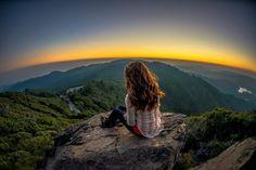 Chica observando un atardecer en una montaña