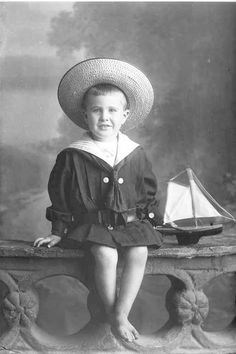 Full length portrait of Master Parker seated on a low wall, wearing a sailor suit and large brimmed, straw hat, bare feet and holding a toy boat in his hand, 1910