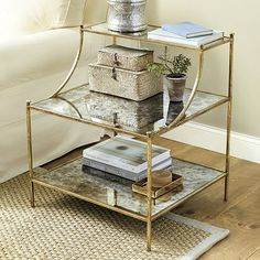 With its stepped back glass shelves, our Emeline Side Table creates lots of storage and display in an airy, elegant design. The slender legs and curved arms are topped with button finials for a dressy finishing touch.