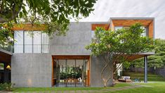 Rows of pivoting glass doors can be opened to allow air to flow through living spaces that open onto courtyards, terraces and lush gardens at this house in the Indonesian city of Semarang.