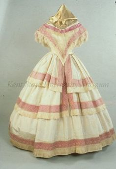In the Swan's Shadow: Kent State University.  Date: 1855-1860  Culture: American, attributed  Description: White silk taffeta. Bodice: wide neck. V waist, short sleeves. Skirt: full with 3 tiers fringed with magenta ribbon covered with net lace and fringe. Bib: silk net and lace.