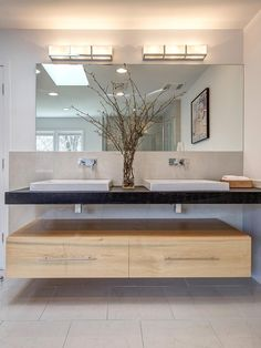 A double sink is mirrored on top and bottom with contemporary floating wood cabinets and rectangular lights overhead.
