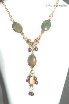 Halsband med grön Opal halvädelstenar, bruna sötvattenpärlor och rund beige sötvattenpärla. Infattning med Swarovski stenar håller smycket ihop