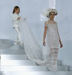Model perfection: Cara Delevingne gracefully walked down the steps in Karl Lagerfeld for Chanel fashion show, with a young boy carrying her ...