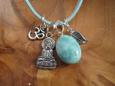 A beautiful Buddha necklace dangles with a turquoise stone, silver leaf and Om charm.