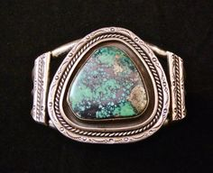 This is a fabulous Old Pawn vintage Navajo sterling silver cuff bracelet featuring a large, rare Morenci turquoise cabochon!  The Morenci turquoise mine in Arizona produced a turquoise that is light to bright blue in hue. This stone has an unusual matrix of irregular quartz and pyrite that, when polished, often resembles silver. One of the first American turquoises to come to the market, Morenci is highly valued and difficult to obtain because the Morenci mine is now closed and buried under…
