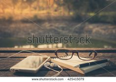 Smartphone with in ear headset, opened notebook, pen, and glasses on rustic wood table in morning time with vintage filter effect