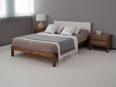 Natural Bed Company Sol Bed with a solid walnut frame and soft ivory headboard.