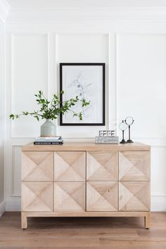 Geometric cabinet front + faceted living room cabinet + white millwork on the walls + white wainscoting on full wall + living room decor + vase of greenery on top of a stack of books + Console table styling decor + living room accessories Side Board, Sideboard Dekor, Living Room Sideboard Ideas, Painted Sideboard, Console Table Styling, White Console Table, Wooden Console, Decoration Hall, Hallway Console
