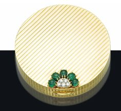 A RETRO GOLD, EMERALD AND DIAMOND COMPACT, BY VAN CLEEF & ARPELS   The gold reeded circular case applied with diamond and cabochon emerald detail, opening to reveal a mirror in the lid bearing the inscription 'Elizabeth F. Coleman - 1956', 7.0 cm, with two fitted pouches, one in black suede, one in brocade  Signed Van Cleef & Arpels, no. NY26960 SO