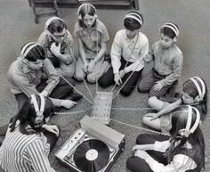 Vintage photo of a group of school children listening intently to a vinyl record. dstele.com