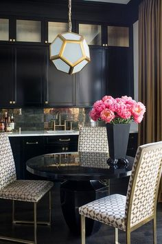 Gold and black dining room features a Robert Abbey Mary Mcdonald Pythagoras Pendant illuminating a round glossy black dining table, Oly Studio Phillippe Dining Table, lined with gold dining chairs.