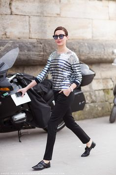 Ece Sukan in a striped sequin shirt, black cigarette pants, and black broques.