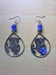 Brincos em tom de cinza e azul com uma coruja e uma aplicação floral azul.