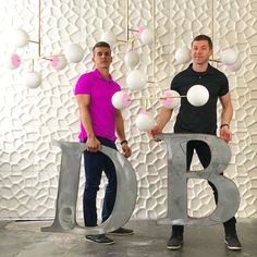 Dutton Brown founders Zach Dutton and Thomas Brown with pink and brass Prisma chandeliers.
