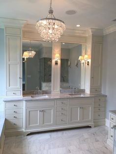 Ivory master bathroom features a Robert Abbey Bling Chandelier illuminating…